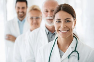 Closeup front view of group of mixed age doctors at a hospital standing in a row and smiling at the camera. Mid 20's intern is in foreground with the rest of the team out of focus.